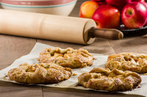 Red apples with apple tarts and rolling pin