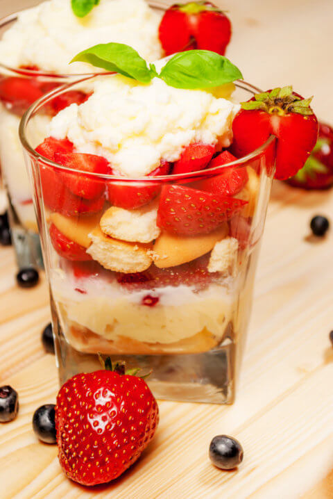 Trifle or cheesecake with strawberry on wood table
